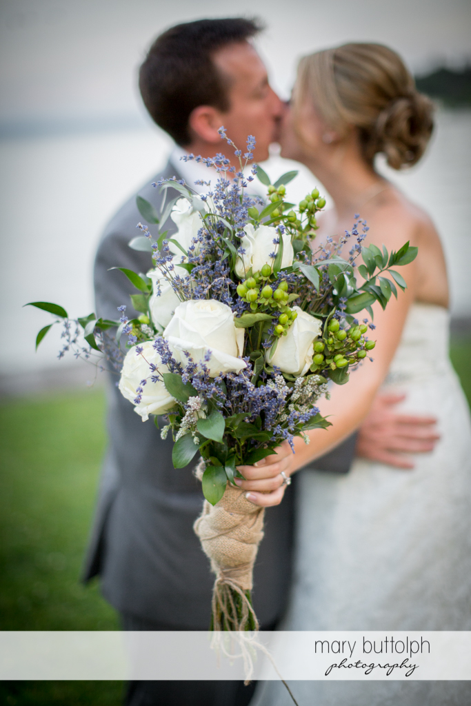 Couple kiss while the bride holds up the bouquet at the Sherwood Inn Wedding