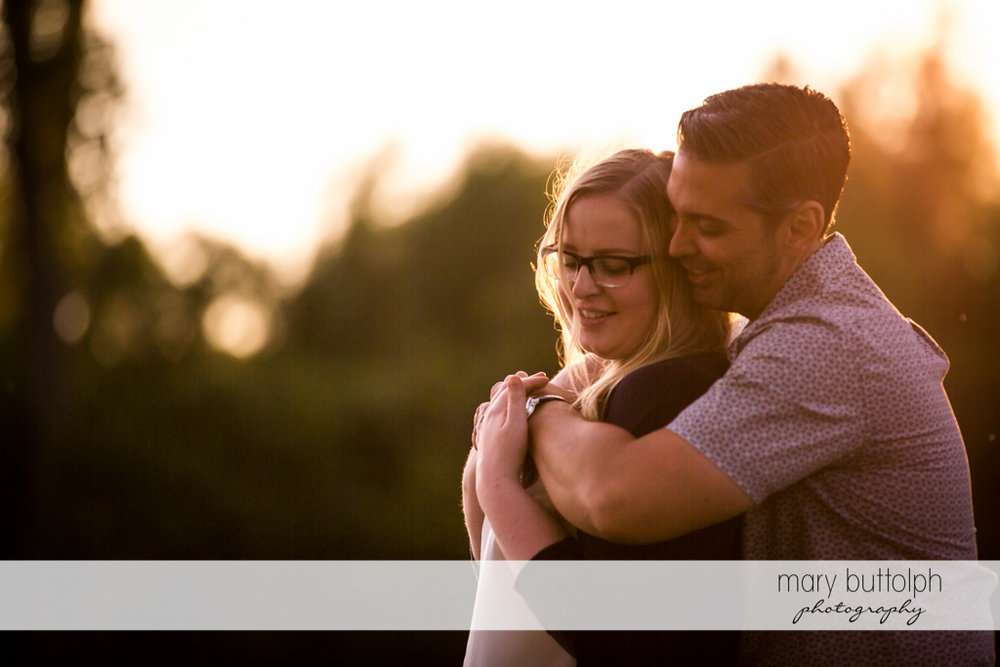 Couple share a tender moment in the garden at Skaneateles Engagement