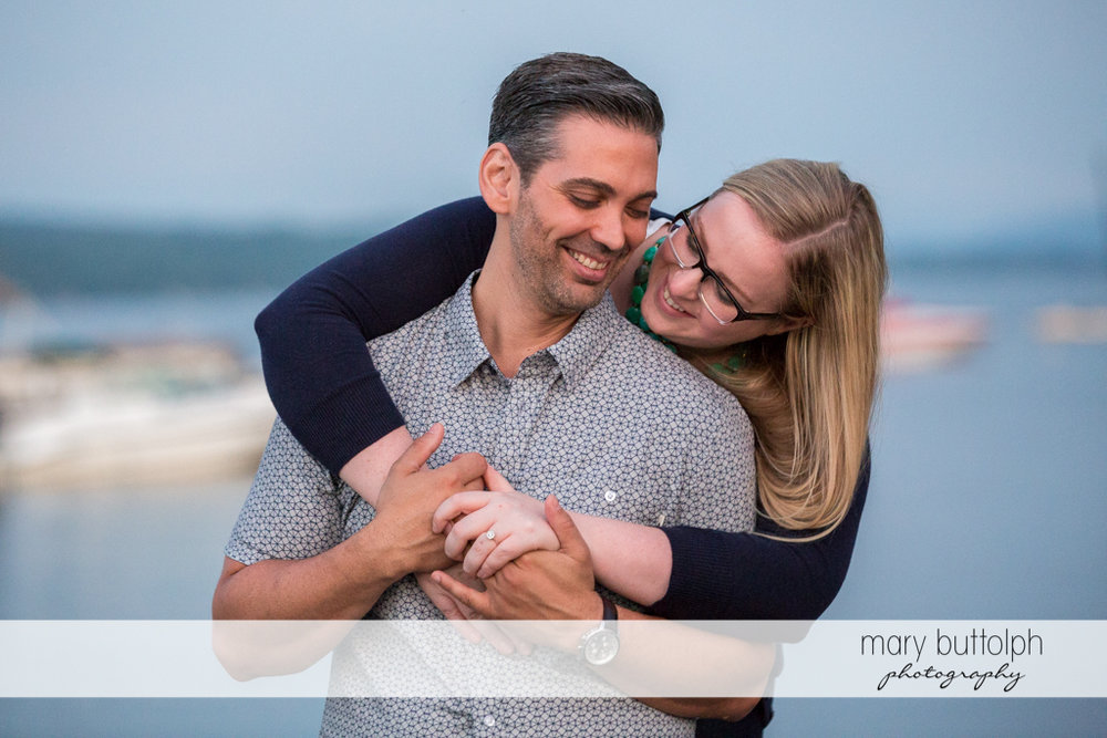 Couple join hands in this beautiful shot in front of the lake at Skaneateles Engagement