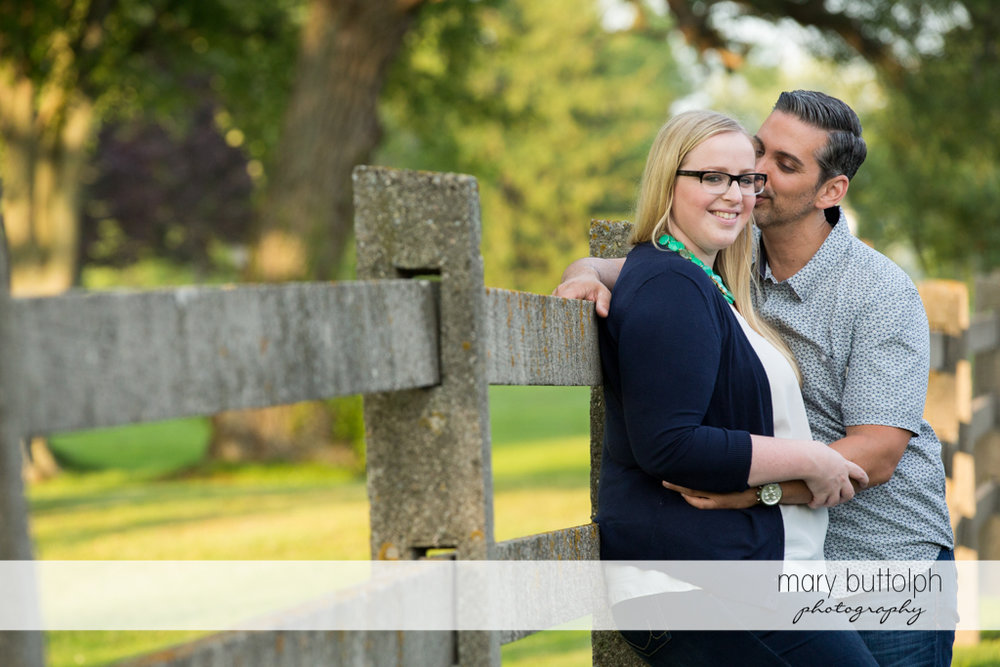 Couple enjoying the view as they stand near a fence at Skaneateles Engagement