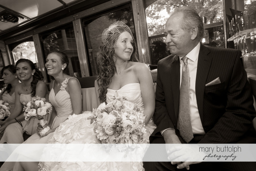 Bride sits next to her father and the bridesmaids at the Inns of Aurora Wedding