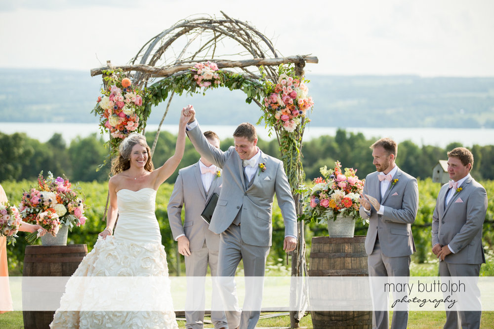 Couple raise their hands in the garden at the Inns of Aurora Wedding