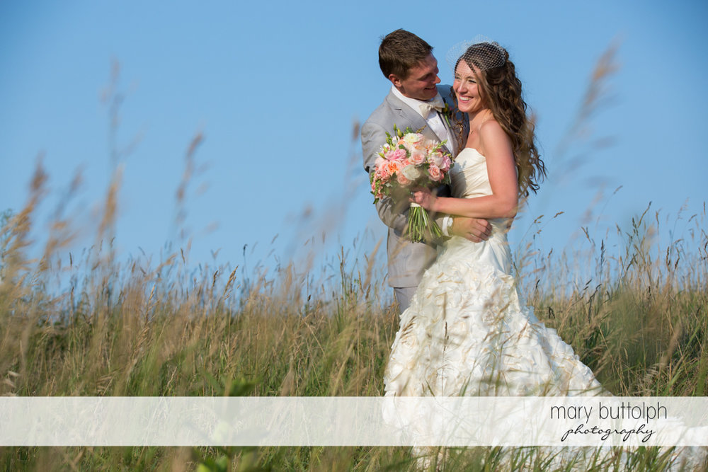 Couple pose in the field at the Inns of Aurora Wedding