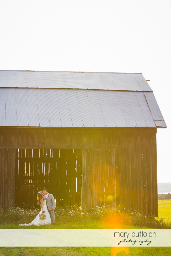 Long shot of the kissing couple in front of an old barn at the Inns of Aurora Wedding
