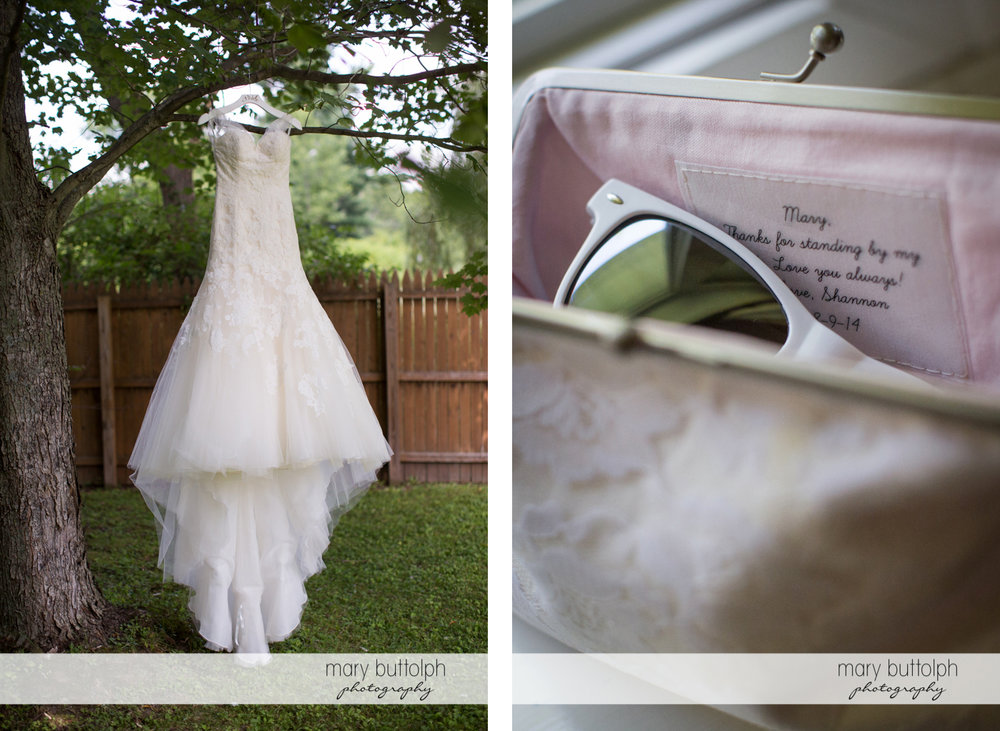 Bride's wedding dress hangs from a tree while her handbag contains a pair of sunglasses at Arrowhead Lodge Wedding