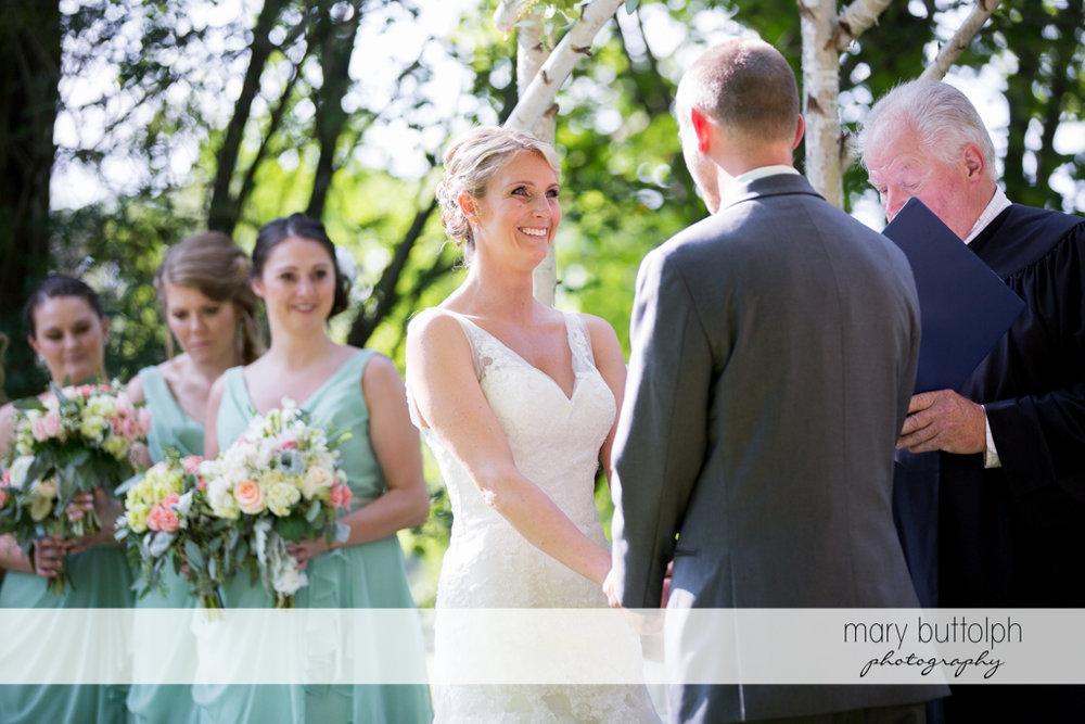 Bride faces the groom in the garden at Arrowhead Lodge Wedding