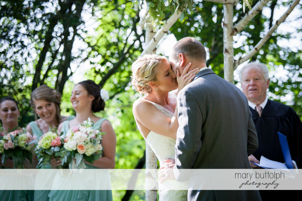 Couple kiss in front of the bridesmaids and the wedding officiant at Arrowhead Lodge Wedding