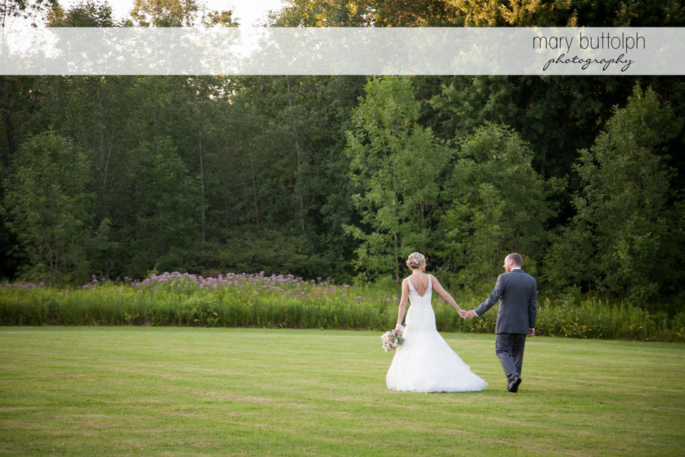 Couple stroll in the garden at Arrowhead Lodge Wedding