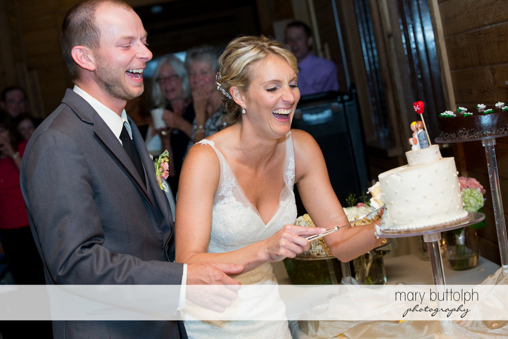 Bride slices the wedding cake as the groom looks on at Arrowhead Lodge Wedding
