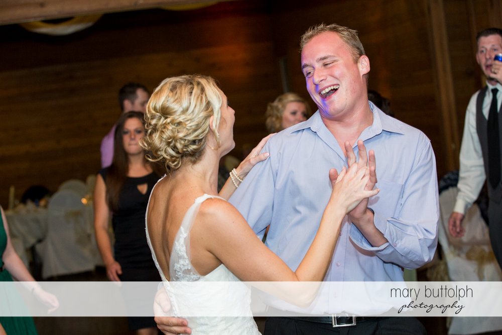 Bride dances with a guest at the wedding venue at Arrowhead Lodge Wedding