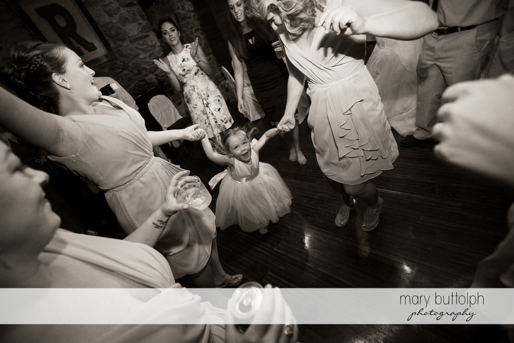 Guests dance with a young girl at the wedding venue at Arrowhead Lodge Wedding