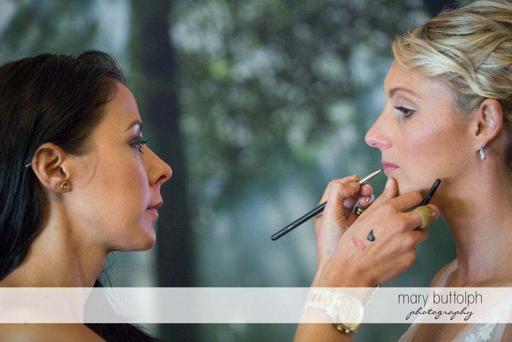 Bride gets a makeover from a friend at Arrowhead Lodge Wedding