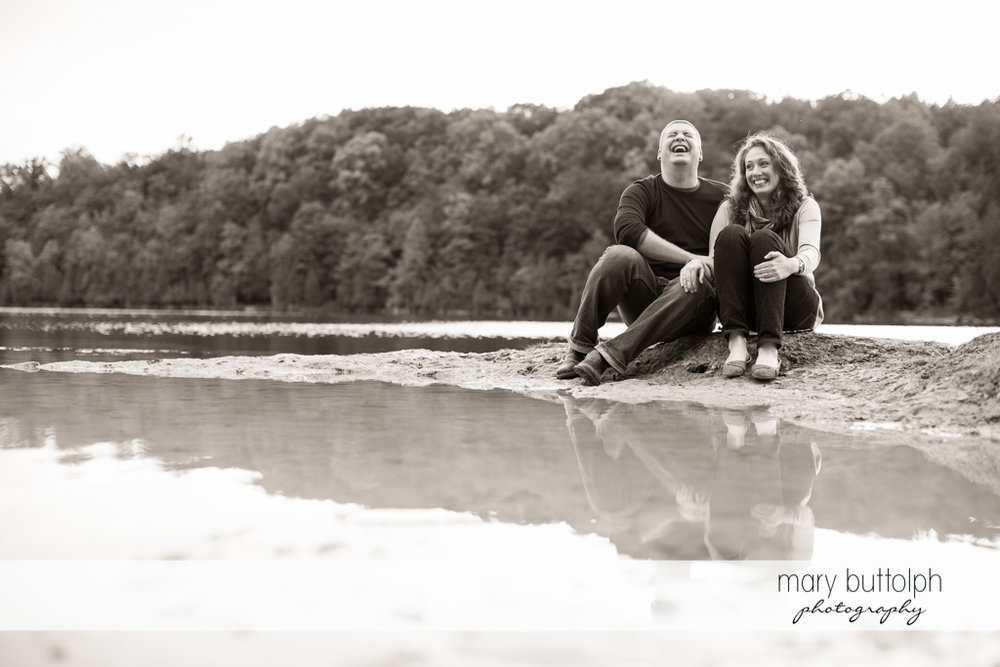 Couple sit along the shore with the forest behind them at Green Lakes State Park Engagement