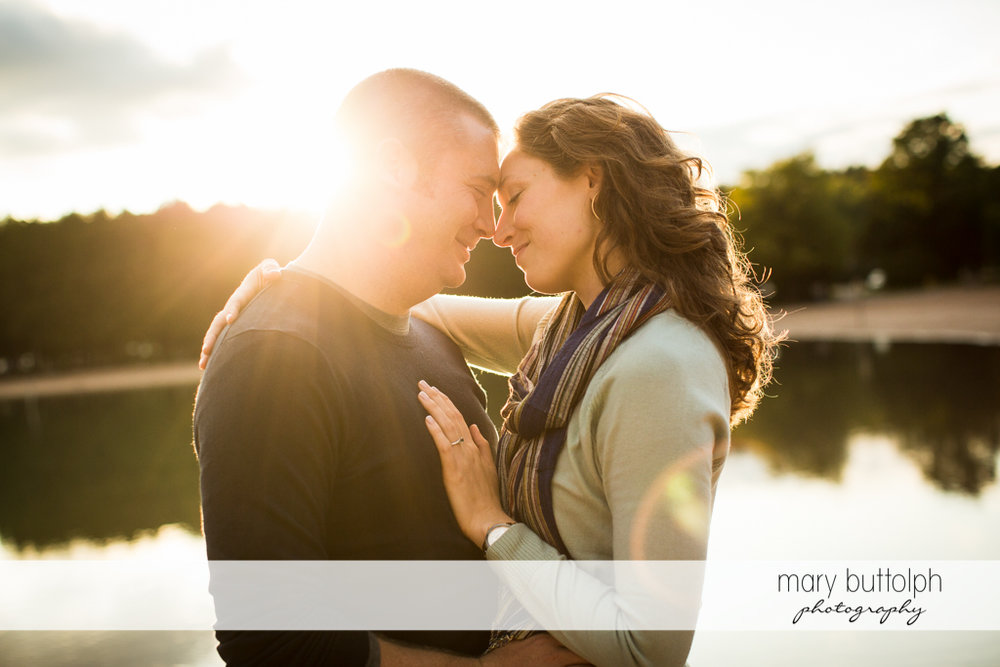 Couple kiss in front of the lake at Green Lakes State Park Engagement