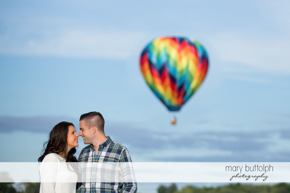 Couple rub noses in front of a hot air balloon at Skaneateles Country Club Engagement