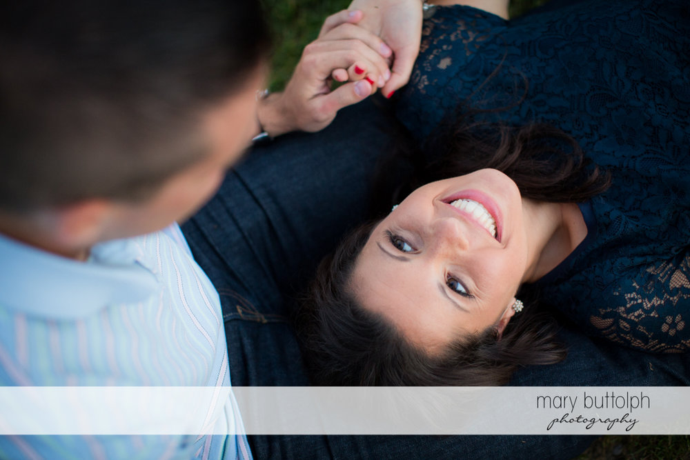 Woman stares at the man while lying on the grass in the park at Skaneateles Country Club Engagement