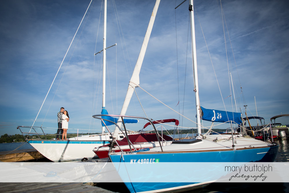 Couple pose in front of sailboats at Skaneateles Country Club Engagement