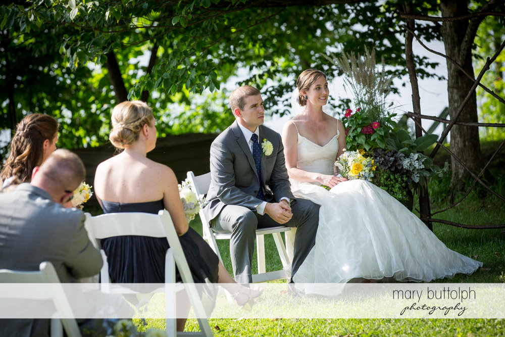 Couple listen to the wedding officiant as guests look on at the Hamilton Inn Wedding