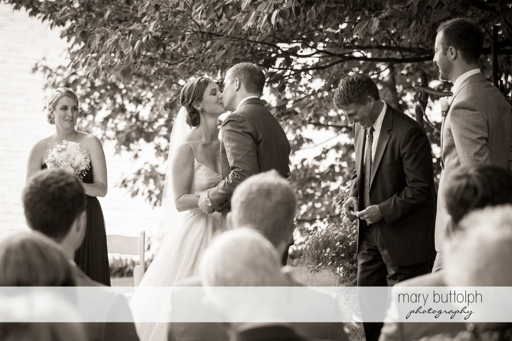 Couple kiss in the garden as guests look on at the Hamilton Inn Wedding
