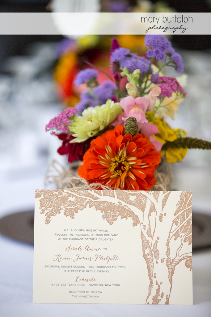 Close up shot of the colorful bouquet and the wedding invitation at the Hamilton Inn Wedding