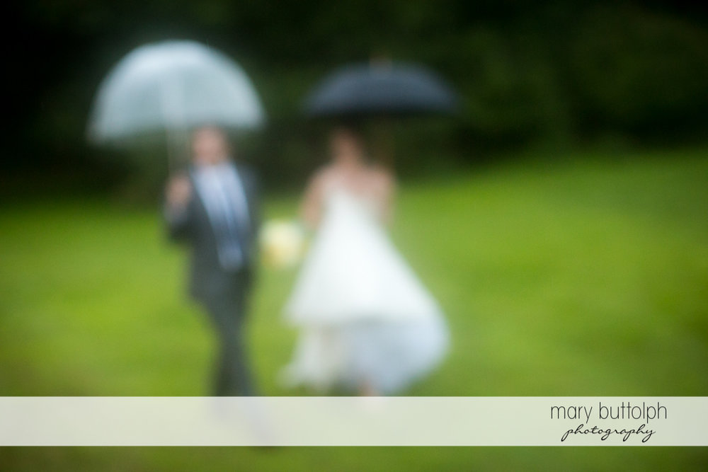 Trick shot of the couple with umbrellas in the garden at the Hamilton Inn Wedding