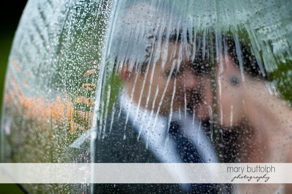 The rain falls on the couple's transparent umbrella at the Hamilton Inn Wedding