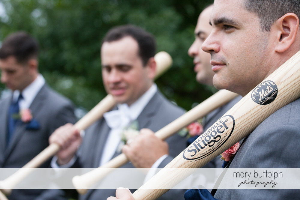 Groom and his groomsmen hold baseball bats at the Inns of Aurora Wedding
