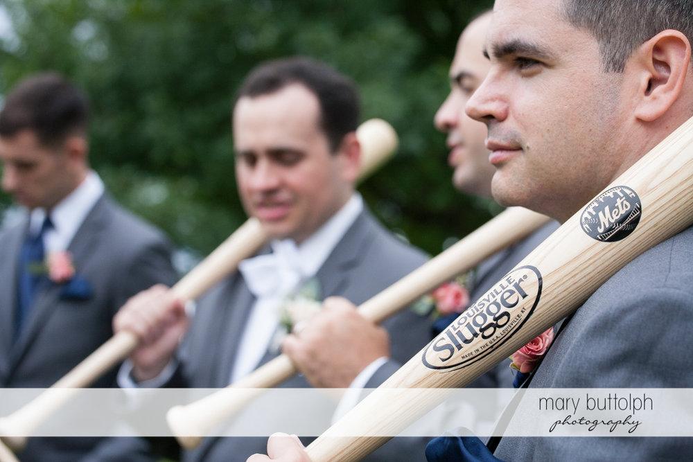 Groom and his groomsmen hold baseball bats at the Inns of Aurora Wedding