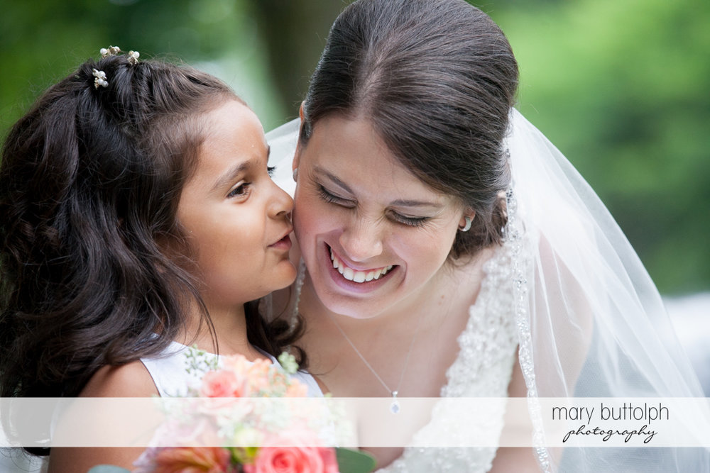 Young girl whispers something funny to the bride at the Inns of Aurora Wedding