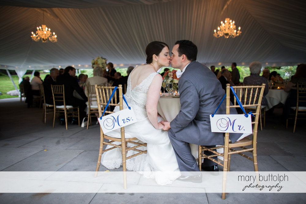 Couple kiss as they sit on designated chairs at the Inns of Aurora Wedding