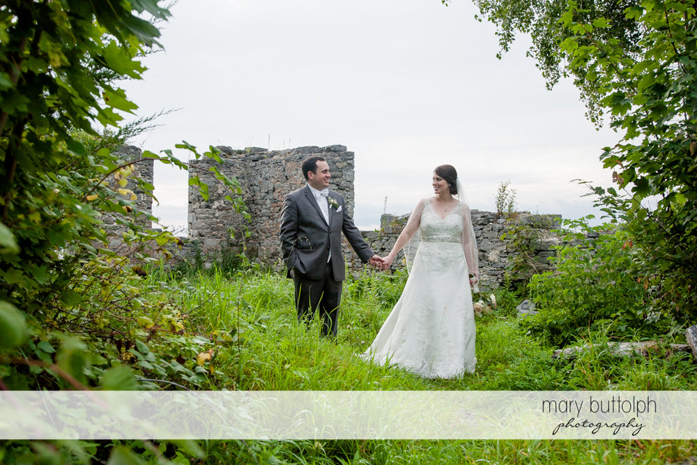 Couple pose in front of the ruins at the Inns of Aurora Wedding