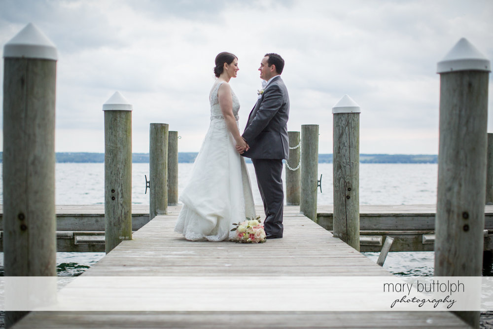 Couple hold hands on the docks at the Inns of Aurora Wedding