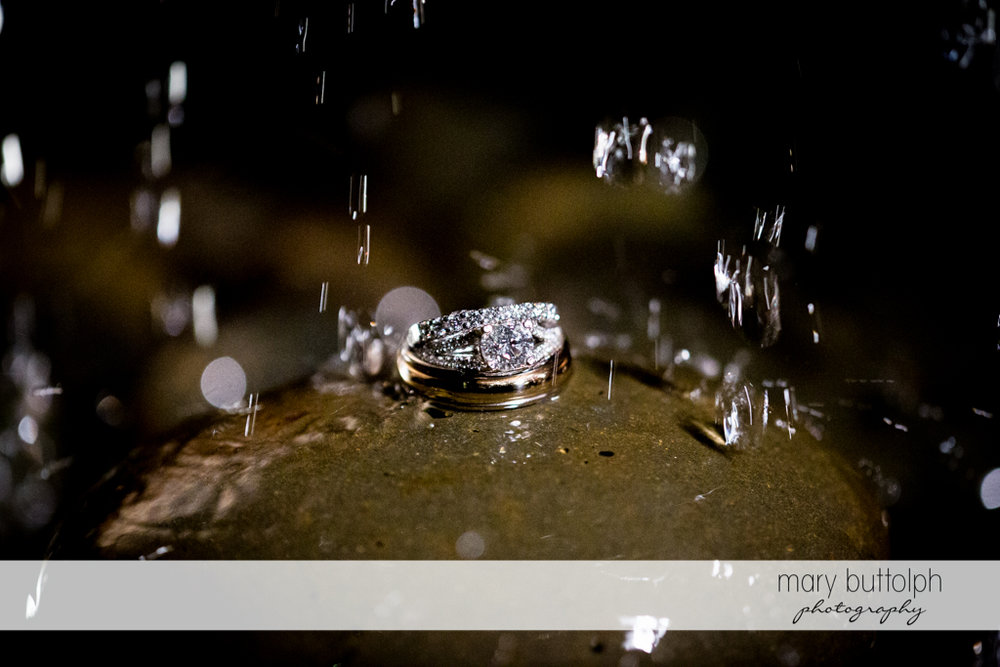 Rain falls on the couple's wedding rings at the Inns of Aurora Wedding