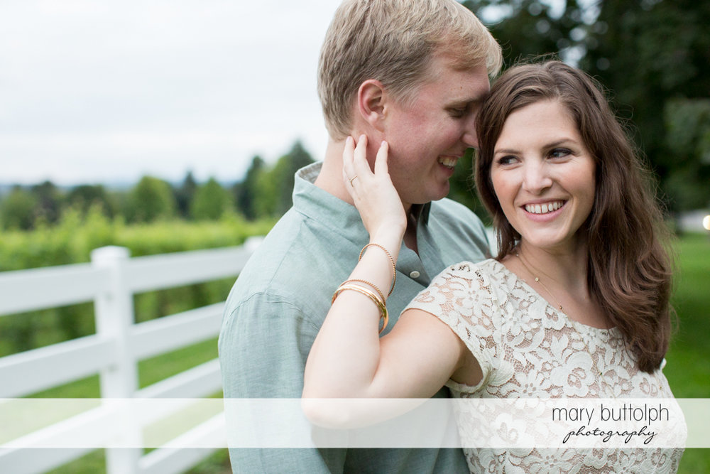 Couple pose in front of a fence at Hobbit Hollow House Engagement