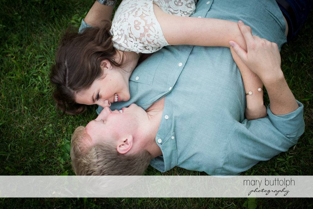 Couple rub noses while lying on the grass at Hobbit Hollow House Engagement