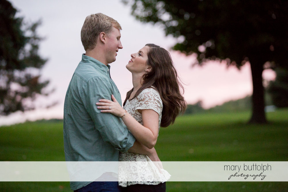 Couple embrace in the meadow at Hobbit Hollow House Engagement