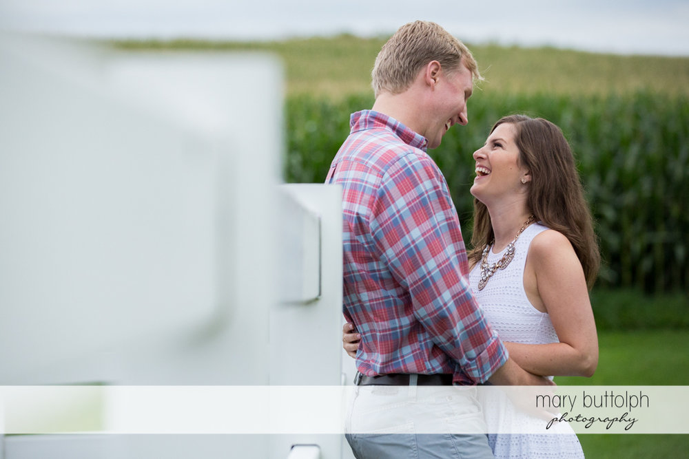 Couple stand near the fence in the vineyard at Hobbit Hollow House Engagement