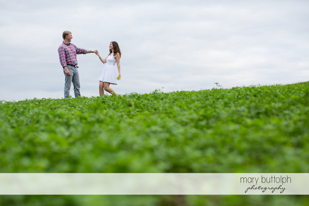 Couple frolic in the meadow at Hobbit Hollow House Engagement