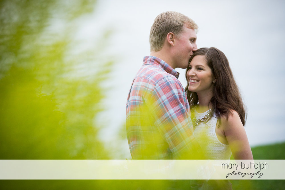 Couple stand near plants at Hobbit Hollow House Engagement