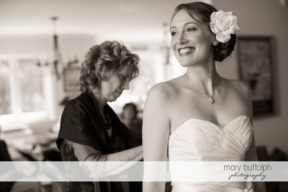 Bride smiles as her mother adjusts her wedding gown at Anyela's Vineyards Wedding