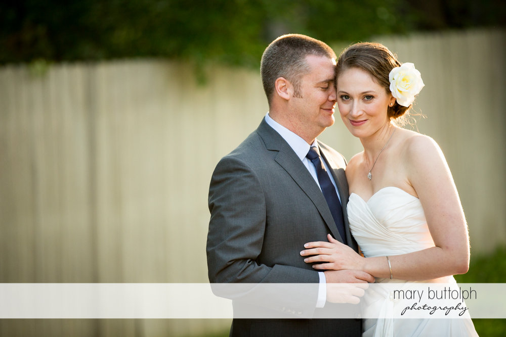 Couple stand in front of a wooden fence at Anyela's Vineyards Wedding