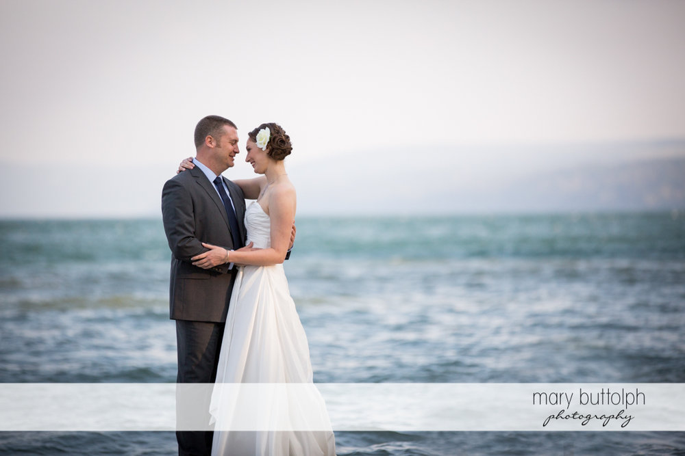Couple pose by the lake at Anyela's Vineyards Wedding