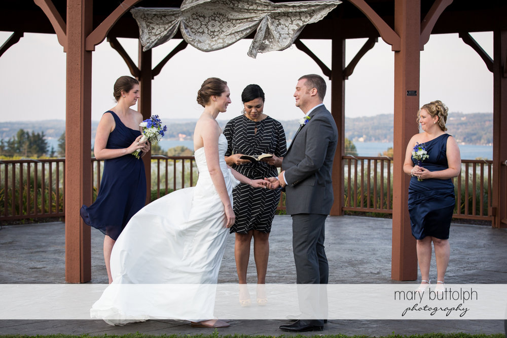 Couple hold hands in front of the wedding officiant at Anyela's Vineyards Wedding