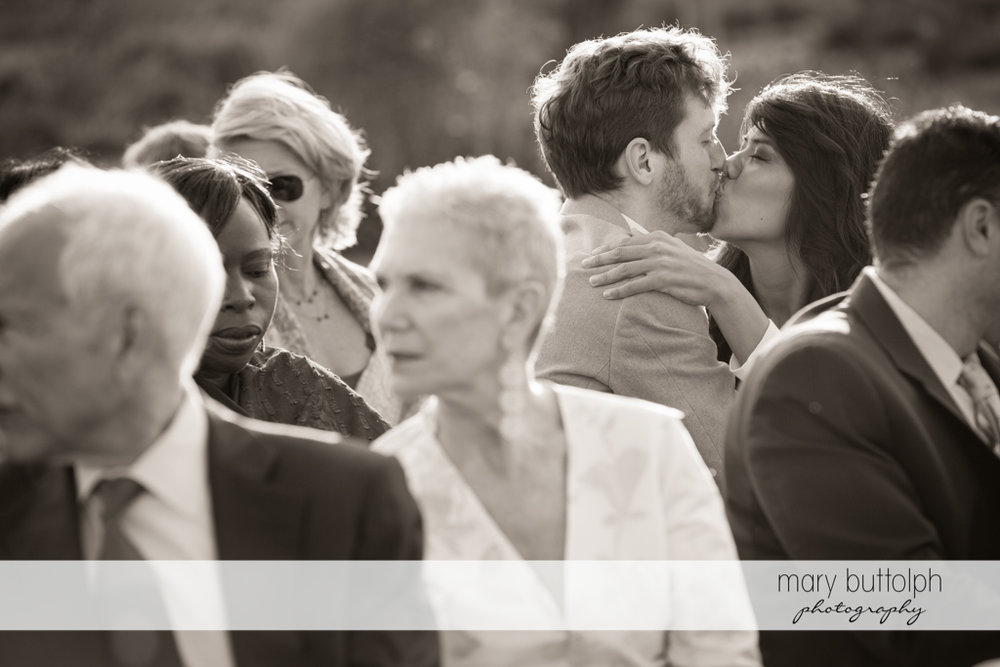 A couple kiss during the wedding ceremony at Anyela's Vineyards Wedding