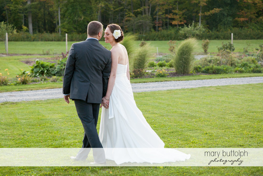 Couple take a stroll in the garden at Anyela's Vineyards Wedding