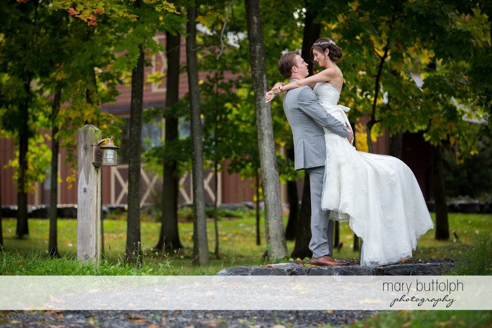 Groom carries bride near the trees at Anyela's Vineyards Wedding