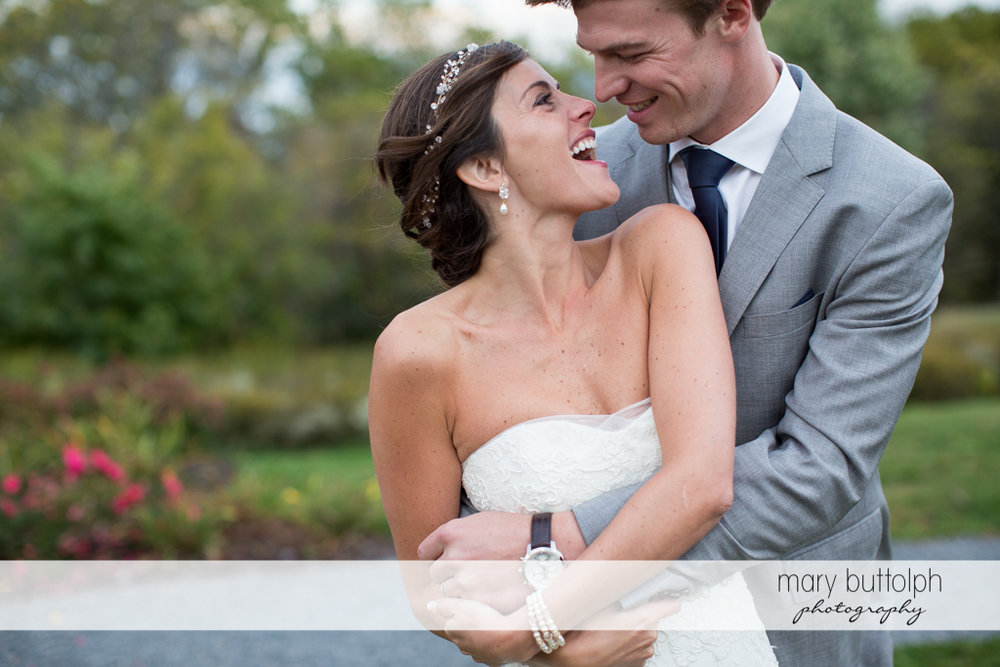 Couple share a happy moment in the garden at Anyela's Vineyards Wedding