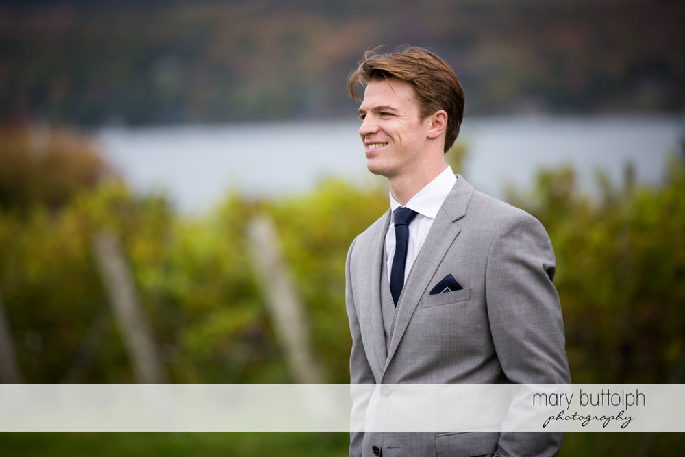 Groom stands in front of the lake at Anyela's Vineyards Wedding