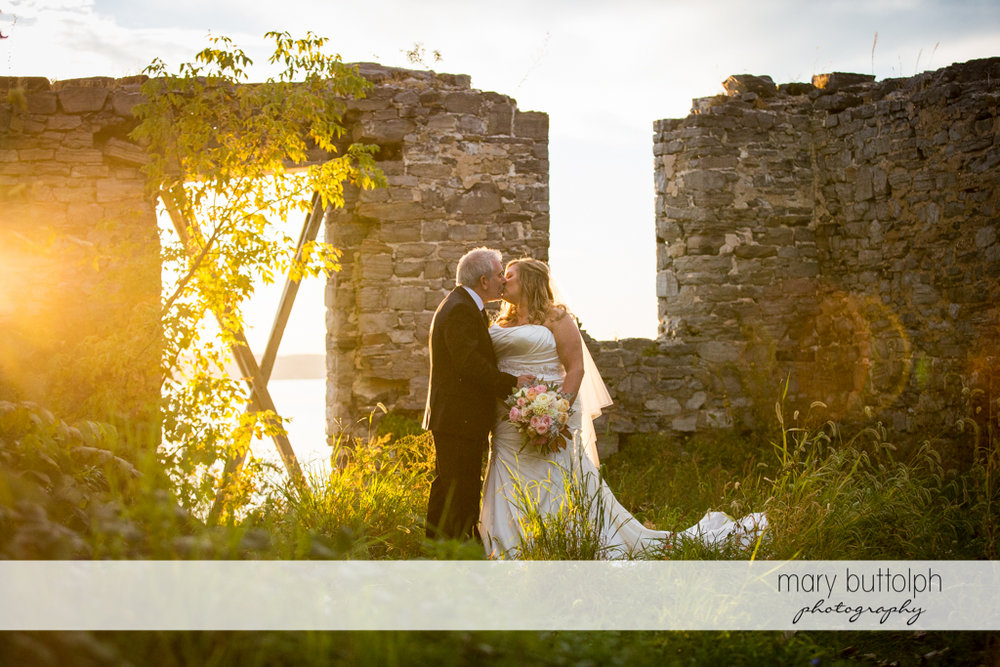 Couple kiss in front of the ruins at the Inns of Aurora Wedding