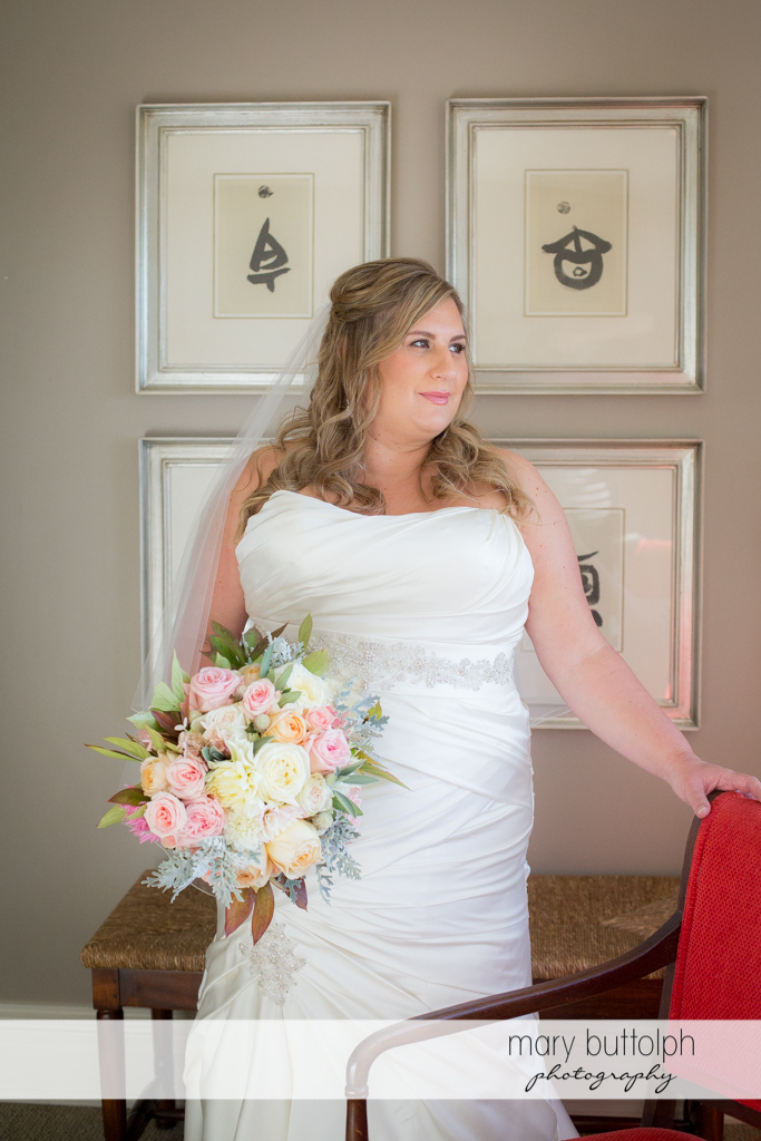 Bride with bouquet stands in front of paintings at the Inns of Aurora Wedding